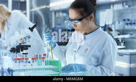 Female Research Scientist Uses Micropipette Filling Test Tubes in a Big Modern Laboratory. In the Background Scientists - Stock Photo