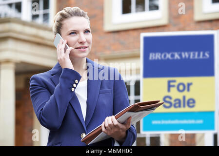 Female Realtor On Phone Outside Residential Property For Sale - Stock Photo