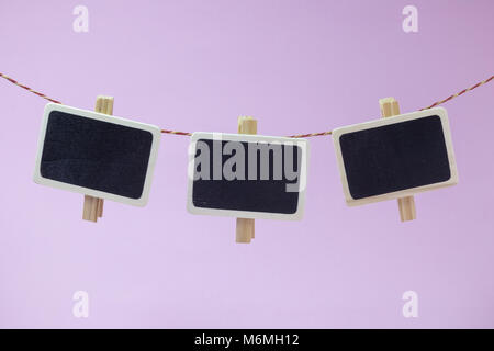 Clothespins with blank photo frames on rope on pastel pink background minimal concept - Stock Photo