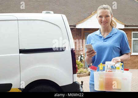 Portrait Of Woman Running Mobile Cleaning Business Checking Text Messages - Stock Photo