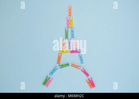 Flat lay of colorful clothespins in form of eiffel tower on pastel blue background. Minimal concept - Stock Photo