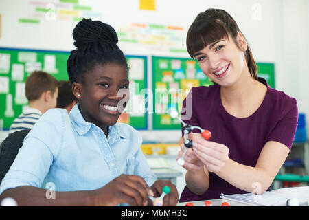 Portrait Of Female Pupil And Teacher Using Molecular Model Kit In Science Lesson - Stock Photo