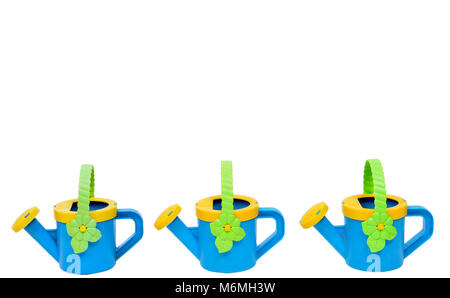 Horizontal shot of a watering pail border across the bottom consisting of three blue and yellow watering cans with - Stock Photo
