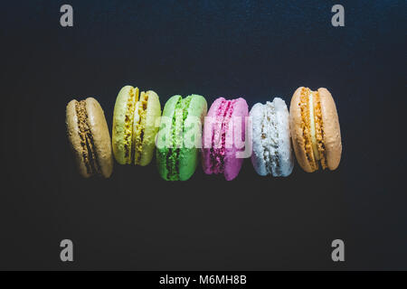 High detailed colorful macarons on black background minimal concept - Stock Photo