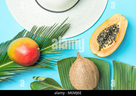 Ripe Juicy Mango Halved Papaya Coconut on Large Palm Leaf Straw Sun Hat on Blue Background. Summer Vacation Relaxation - Stock Photo