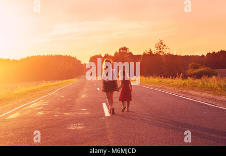 Silhouette two little girls walking on the road . Sisters enjoyed a Holiday over blurred summer nature. Concept - Stock Photo