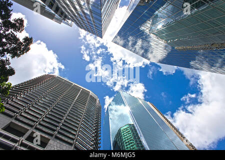 View looking up at blue cloudy sky through skyscrapers reflecting clouds and other buildings in CBD Brisbane Queensland - Stock Photo