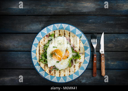 Fried eggs on flour tortilla with green salad and cheese. Useful breakfast or lunch idea. Fork knife and beautiful - Stock Photo