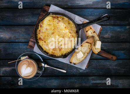 Breakfast. Classic omelette on a frying pan on a wooden stand with toast and coffee. Colored wooden background. - Stock Photo