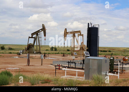 Two oil - gas well pump jack at drilling site with equipment and holding tanks on praries with low hill behind and blue cloudy sky