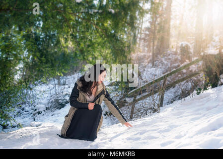 Young brunette woman, dressed in a winter jacket and  black skirt, in a squat position, reaching for snow, on a - Stock Photo