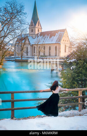 Rear view of an attractive young woman, dressed elegantly, admiring the blue water of the Blautopf spring, on a sunny day, in Blaubeuren, Germany.