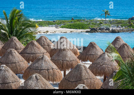 Straw umbrellas on beautiful sunny beach by the turquoise sea, ocean - Stock Photo
