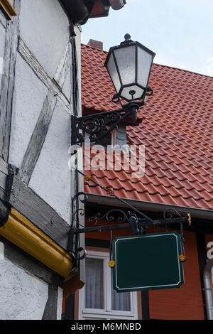 Decorative cast iron lantern and a sign on the wall of the German half-timbered houses on the background of tiled - Stock Photo