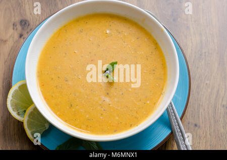 lentil soup in white plate on table. Traditional soup made with potato, oil, onion, tomato paste, spices. Top view. - Stock Photo