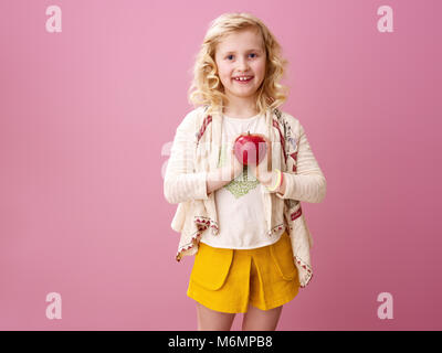 Pink mood. smiling stylish girl with wavy blonde hair on pink background holding an apple - Stock Photo