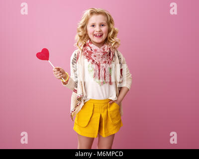 Pink mood. smiling stylish girl with wavy blonde hair isolated on pink with heart shaped lollipop - Stock Photo