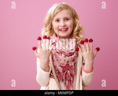 Pink mood. Portrait of happy stylish child with wavy blonde hair isolated on pink with raspberries on the fingers - Stock Photo