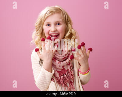 Pink mood. smiling stylish girl with wavy blonde hair on pink background eating raspberries on the fingers - Stock Photo