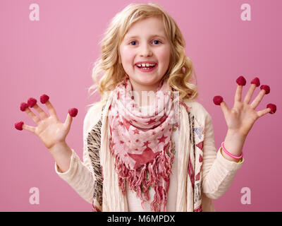 Pink mood. Portrait of happy stylish girl with wavy blonde hair on pink background showing raspberries on the fingers - Stock Photo