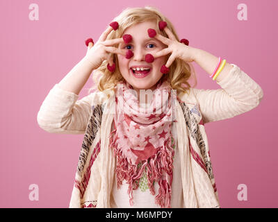 Pink mood. Portrait of smiling modern child with wavy blonde hair isolated on pink background with raspberries on - Stock Photo