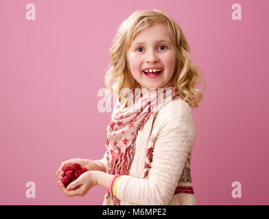 Pink mood. Portrait of happy modern girl with wavy blonde hair isolated on pink background with raspberries - Stock Photo
