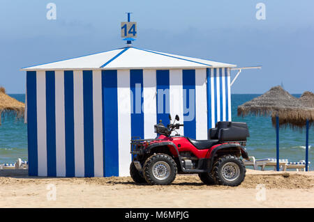 A red four-wheeled beach vehicle in front of a hut on a sandy beach - Stock Photo