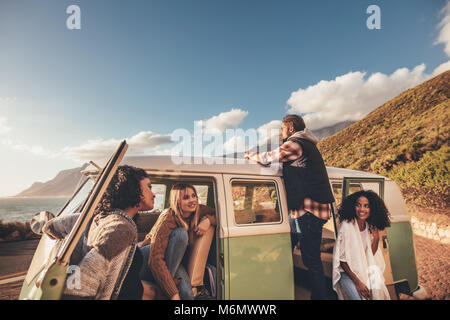 Friends on roadtrip relaxing by the van. Group of man and women travelling together in an old minivan. - Stock Photo