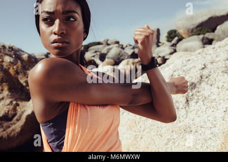 African woman stretching arms at the beach. Fitness female doing warmup workout and looking away outdoors. Closeup - Stock Photo