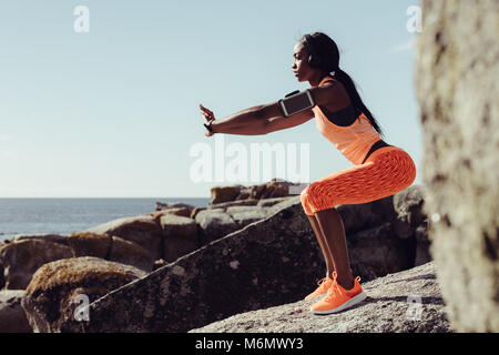 Woman runner doing stretching exercises. Woman doing warm up stretches on rocks at the beach. - Stock Photo