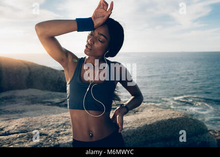 Fitness woman looking tired after intense physical training. Sportswoman standing over rocks at the beach with hand - Stock Photo