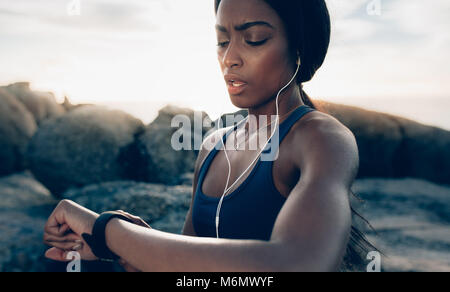 Close up of young fitness woman looking at her smart watch while taking a break from outdoor workout. Sportswoman - Stock Photo