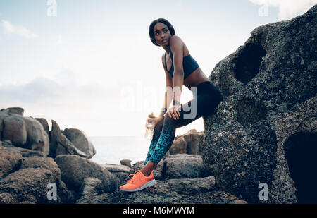 Fitness woman with a water bottle resting over a rock. Female with slim body relaxing after workout outdoors. - Stock Photo