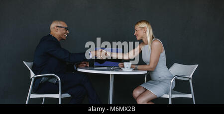 Two business people shaking hands after a successful meeting. Businessman and woman hand shake at cafe over a deal. - Stock Photo