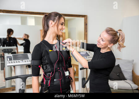Portrait of personal trainer putting diodes on woman ems jacket - Stock Photo