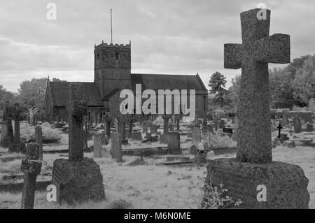 Black and white picture of graves and headstones in the churchyard cemetery of the grade I listed St Andrews church - Stock Photo
