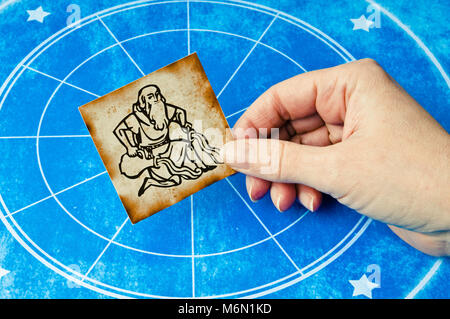 hand holding a card with sign of aquarius - Stock Photo