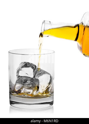 Pouring whiskey from bottle into glass with ice - Stock Photo