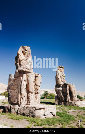 Luxor, Egypt. Colossi of Memnon,  two massive stone statues of the Pharaoh Amenhotep III, who reigned in Egypt during - Stock Photo