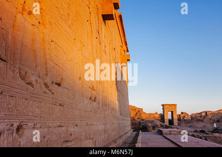 Bas reliefs outside the Temple of Hathor with one of the compound´s gateways in background at sunset. Dendera, Egypt - Stock Photo