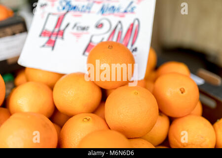 Close up of fresh juicy large Spanish Naval oranges on a traditional market stall in England, United Kingdom - Stock Photo