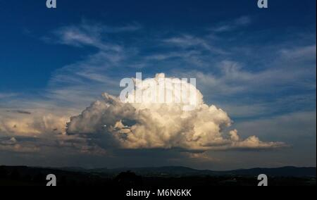 Storm cloud over the countryside. Cloud illuminated by sun. Blue sky above. - Stock Photo