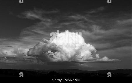 Storm cloud over the countryside. Cloud illuminated by sun. Black and white version. - Stock Photo