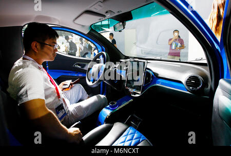 Beijing, China. 3rd Aug, 2017. A visitor experiences inside an electric car at the future vehicle show in Shanghai, - Stock Photo