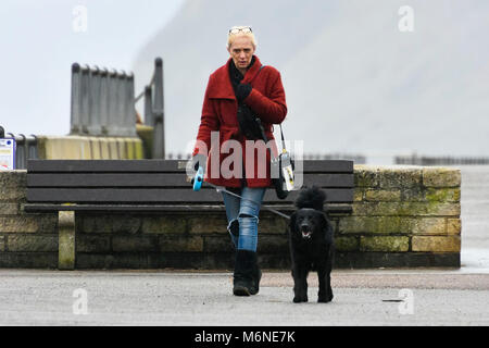 West Bay, Dorset, UK.  5th March 2018.  UK Weather.  A dog walker walking along the seafront in the rain at West - Stock Photo