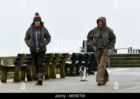 West Bay, Dorset, UK.  5th March 2018.  UK Weather.  A couple walking along the seafront in the rain at West Bay - Stock Photo