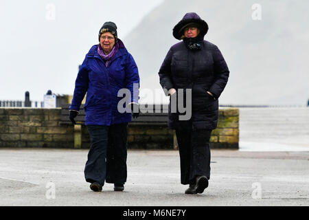 West Bay, Dorset, UK.  5th March 2018.  UK Weather.  Two women walking along the seafront in the rain at West Bay - Stock Photo