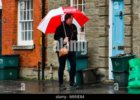 Bridport, Dorset, UK.  5th March 2018.  UK Weather.  A woman walking in the pouring rain with an umbrella in South - Stock Photo