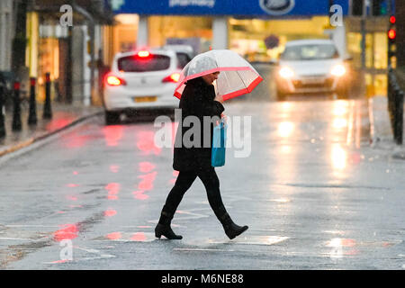 Bridport, Dorset, UK.  5th March 2018.  UK Weather.  A woman walking across the road in the pouring rain with an - Stock Photo