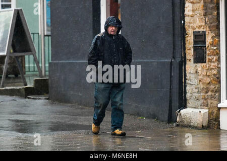 Bridport, Dorset, UK.  5th March 2018.  UK Weather.  A man walking in the pouring rain in South Street in Bridport - Stock Photo